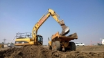 Cat 324DL Excavator loading a truck